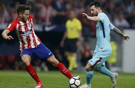 Barcelona's Lionel Messi, right, vies for the ball with Atletico Madrid's Saul Niguez during a Spanish La Liga soccer match between Atletico Madrid and Barcelona at the Metropolitano stadium in Madrid, Saturday, Oct. 14, 2017. (AP Photo/Francisco Seco)