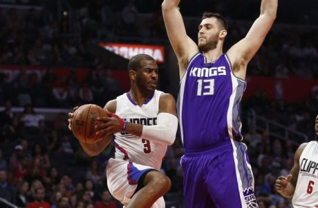Los Angeles Clippers guard Chris Paul, left, prepares to pass to forward Luc Mbah a Moute (not shown) around Sacramento Kings center Georgios Papagiannis, right, during the second half of an NBA basketball game, Sunday, March 26, 2017, in Los Angeles. (AP Photo/Danny Moloshok)