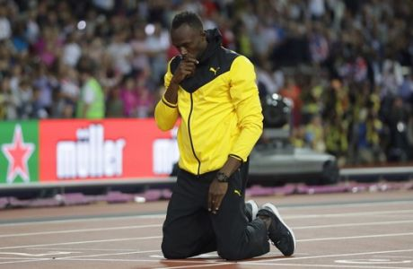 Jamaica's Usain Bolt kneels down during a lap of honor at the end of the World Athletics Championships in London Sunday, Aug. 13, 2017. (AP Photo/Matt Dunham)