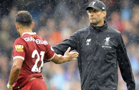 Liverpool's coach Juergen Klopp, right, and player Alex Oxlade-Chamberlain, left, shake hands during heavy rainfall after the English Premier League soccer match between Manchester City and Liverpool at the Etihad Stadium in Manchester, England, Saturday, Sept. 9, 2017. Manchester defeated Liverpool by 5-0. (AP Photo/Rui Vieira)