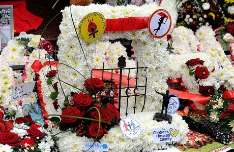 Tributes are laid at the memorial of the Hillsborough disaster outside Anfield before the English Premier League soccer match between Liverpool and Manchester City at Anfield in Liverpool, England, Sunday April. 13, 2014. (AP Photo/Clint Hughes)