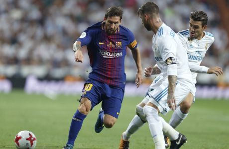 Barcelona's Lionel Messi, left, vies for the ball with Real Madrid defenders during the Spanish Super Cup second leg soccer match between Real Madrid and Barcelona at the Santiago Bernabeu Stadium in Madrid, Wednesday, Aug. 16, 2017. Real Madrid won 5-1 on aggregate. (AP Photo/Francisco Seco)