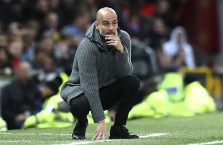Manchester City coach Pep Guardiola looks from the touchline during the English Premier League soccer match between Manchester United and Manchester City at Old Trafford Stadium in Manchester, England, Wednesday April 24, 2019. (AP Photo/Jon Super)