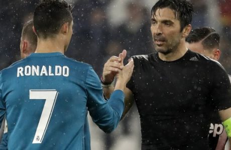 Juventus goalkeeper Gianluigi Buffon, right, shakes hands with Real Madrid's Cristiano Ronaldo after the Champions League, round of 8, first-leg soccer match between Juventus and Real Madrid at the Allianz stadium in Turin, Italy, Tuesday, April 3, 2018. Real won 3-0. (AP Photo/Luca Bruno)