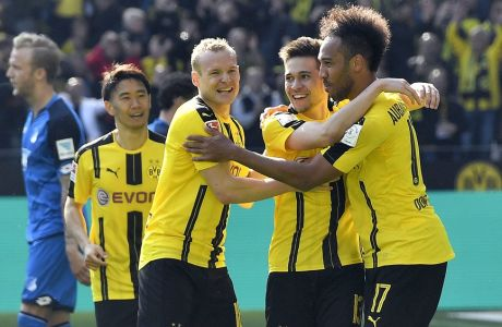 Dortmund's Pierre-Emerick Aubameyang, right, is celebrated by Dortmund's Sebastian Rode and Dortmund's Raphael Guerreiro after scoring during the German Bundesliga soccer match between Borussia Dortmund and TSG Hoffenheim in Dortmund, Germany, Saturday, May 6, 2017. Dortmund defeated Hoffenheim with 2-1. (AP Photo/Martin Meissner)