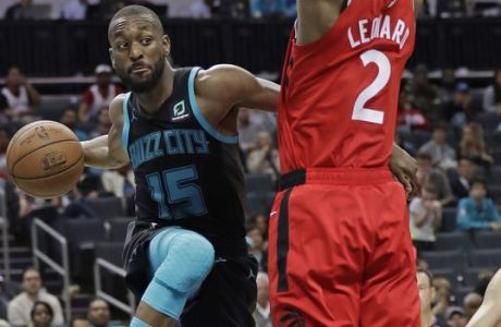 Charlotte Hornets' Kemba Walker (15) tries to pass the ball around Toronto Raptors' Kawhi Leonard (2) during the first half of an NBA basketball game in Charlotte, N.C., Friday, April 5, 2019. (AP Photo/Chuck Burton)