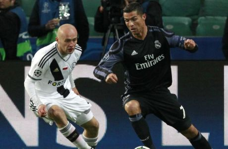 Legia's Michal Pazdan, left, battles for the ball with Real Madrid's Cristiano Ronaldo during the Champions League Group F soccer match between Legia Warsaw and Real Madrid, at Stadion Wojska Polskiego, in Warsaw, Poland, Wednesday, Nov. 2, 2016. The match is played at the empty stadium because of earlier fan trouble during a Champions League match against Borussia Dortmund. (AP Photo/Czarek Sokolowski)