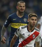 Dario Benedetto of Argentina's Boca Juniors, left, makes a face at Gonzalo Montiel of Argentina's River Plate during the Copa Libertadores final soccer match at the Santiago Bernabeu stadium in Madrid, Spain, Sunday, Dec. 9, 2018. (AP Photo/Thanassis Stavrakis)