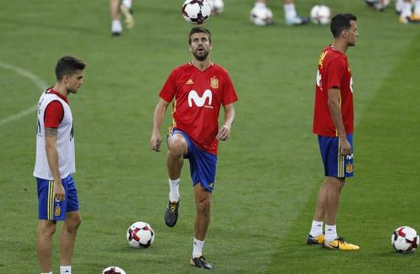 Spain's Gerard Pique, centre, plays with a ball during a training session of the Spanish soccer national team at the Santiago Bernabeu stadium in Madrid, Friday, Sept. 1, 2017.  Spain will play a World Cup Group G qualifying soccer match against Italy on Saturday 2. (AP Photo/Francisco Seco)