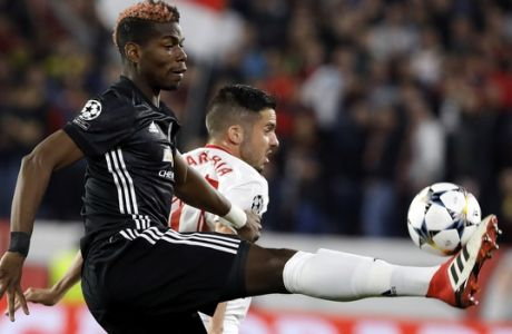 Manchester United's Paul Pogba fights for the ball with Sevilla's Pablo Sarabia, right, during the Champions League round of sixteen first leg soccer match between Sevilla FC and Manchester United at the Ramon Sanchez Pizjuan stadium in Seville, Spain, Wednesday, Feb. 21, 2018. (AP Photo/Miguel Morenatti)