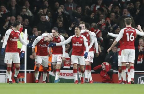 Arsenal's players celebrate the goal of Arsenal's Jack Wilshere, second left, after he scored his side's first goal during the English Premier League soccer match between Arsenal and Chelsea at Emirates stadium in London, Wednesday, Jan. 3, 2018. (AP Photo/Frank Augstein)