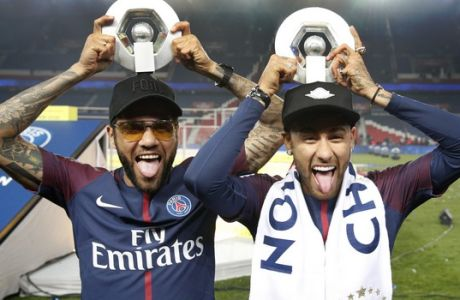 PSG players Neymar, right, and Dani Alves hold their League One winners trophy after the soccer match between Paris Saint-Germain and Stade Rennais at the Parc des Princes stadium in Paris, Saturday May 12, 2018. (AP Photo/Christophe Ena)