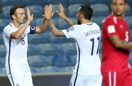 Greece's Vasilis Torosidis, left, celebrates with Kostas Mitroglou after scoring his side's fourth goal during the World Cup Group H qualifying soccer match between Gibraltar and Greece outside Faro, southern Portugal, Tuesday, Sept. 6, 2016. (AP Photo/Armando Franca)