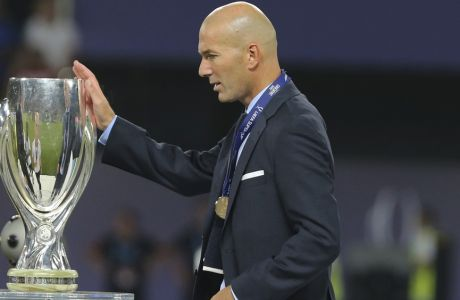 Real Madrid's coach Zinedine Zidane touches the trophy during the Super Cup final soccer match between Real Madrid and Manchester United at Philip II Arena in Skopje, Tuesday, Aug. 8, 2017. Real Madrid defeated Manchester United 2-1. (AP Photo/Boris Grdanoski)