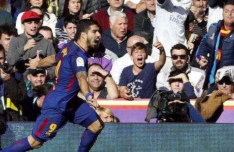 Barcelona's Luis Suarez celebrates after scoring the opening goal during the Spanish La Liga soccer match between Real Madrid and Barcelona at the Santiago Bernabeu stadium in Madrid, Spain, Saturday, Dec. 23, 2017. (AP Photo/Francisco Seco)