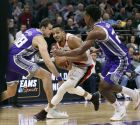 Portland Trail Blazers guard CJ McCollum, center, drives between Sacramento Kings Nemanja Bjelica, left, and Buddy Hield, right, during the second half of an NBA basketball game, Monday, Jan. 14, 2019, in Sacramento, Calif. The Kings won 115-107. (AP Photo/Rich Pedroncelli)