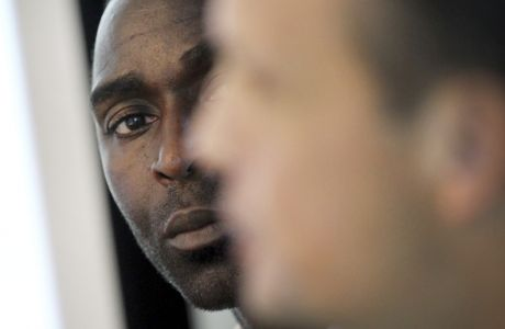 Former Manchester United and England striker Andy Cole, left, looks on as Peter Ter Kulve, president of Unilever, South East Asia and Australasia, right, speaks at a press conference, Monday, Nov. 4, 2013 in Singapore where a Unilever and the Manchester United Partnership was announced.(AP Photo/Wong Maye-E)