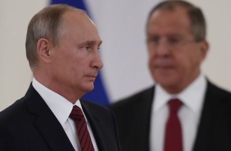 Russian President Vladimir Putin, left, and Foreign Minister Sergey Lavrov stand during a ceremony of presenting ambassador's credentials in the Kremlin in Moscow, Russia, on Tuesday, Oct. 3, 2017. The new U.S. Ambassador to Russia presented his credentials to President Vladimir Putin in the Kremlin on Monday amid investigations into Moscow's meddling in the 2016 U.S. elections. (AP Photo/Pavel Golovkin, Pool)