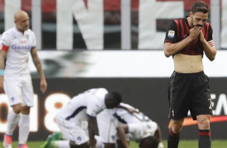 AC Milan's Mattia De Sciglio, right, gestures after Empoli's Mame Baba Thiam, celebrates after scoring in background, during a Serie A soccer match between AC Milan and Empoli, at the San Siro stadium in Milan, Italy, Sunday, April 23, 2017. (AP Photo/Luca Bruno)