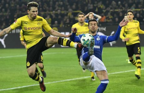 Dortmund's Raphael Guerreiro, left, and Schalke's Matija Nastasic, right, challenge for the ball during the German Bundesliga soccer match between Borussia Dortmund and FC Schalke 04 in Dortmund, Germany, Saturday, Nov. 25, 2017. (AP Photo/Martin Meissner)