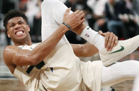 Milwaukee Bucks forward Giannis Antetokounmpo (34) grabs his right ankle after falling to the floor during the fourth quarter of an NBA basketball game against the Brooklyn Nets, Sunday, Feb. 4, 2018, in New York. Antetokounmpo did not return to the game. and the Bucks defeated the Nets 109-94. (AP Photo/Kathy Willens)