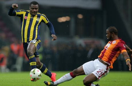 Galatasaray's Aurelien Chedjou, right, and Emmanuel Emenike of Fenerbahce fight for the ball during their Turkish League soccer derby match at the TT Arena stadium in Istanbul, Turkey, Saturday, Oct. 18, 2014.(AP Photo)