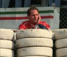 Gerhard Berger, of Austria, watches the race from behind protection tires after breaking the suspension of his Ferrari when he was in second position during the Grand Prix of Italy in Monza Sunday, Sept. 10, 1995. (Ap Photo/Luca Cattaneo)