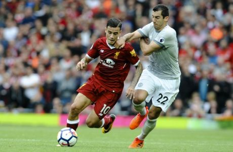 Liverpool's Philippe Coutinho, left, and Manchester United's Henrikh Mkhitaryan, right, battle for the ball during the English Premier League soccer match between Liverpool and Manchester United at Anfield, Liverpool, England, Saturday, Oct. 14, 2017. (AP Photo/Rui Vieira)