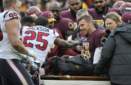 Houston Texans strong safety Kareem Jackson (25) reaches for Washington Redskins quarterback Alex Smith (11) as he leaves the field after an injury during the second half of an NFL football game, Sunday, Nov. 18, 2018 in Landover, Md. (AP Photo/Mark Tenally)