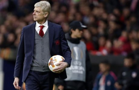 Arsenal manager Arsene Wenger holds the ball during the Europa League semifinal, second leg soccer match between Atletico Madrid and Arsenal at the Metropolitano stadium in Madrid, Spain, Thursday, May 3, 2018. (AP Photo/Francisco Seco)