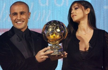 Italy's World Cup-winning captain Fabio Cannavaro is congratuled by actress Monica Bellucci after being awarded the 2006 'Ballon d'Or' (Golden Ball), for best football player of the year, 27 November 2006 in Paris. AFP PHOTO FRANCK FIFE / AFP PHOTO / FRANCK FIFE