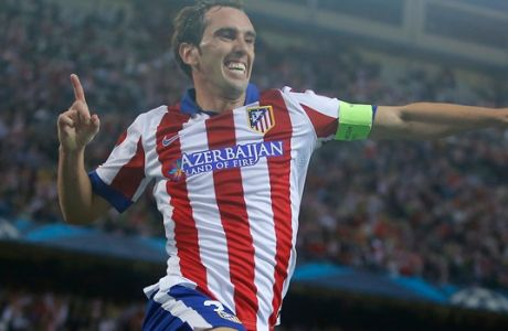 Atletico's Diego Godin, right, celebrates with his teammate Miranda after scoring during the Group A Champions League soccer match between Atletico de Madrid and Malmo at the Vicente Calderon stadium in Madrid, Spain, Wednesday, Oct. 22, 2014. (AP Photo/Andres Kudacki)