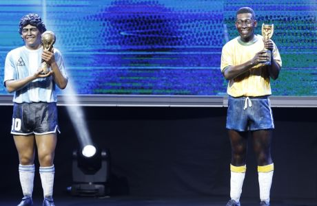 Statues of Argentina's Diego Armando Maradona, left, and Brazil's Pele stand during the drawing ceremony for the Copa Libertadores soccer tournament in Luque, Paraguay, Wednesday, Dec. 20, 2017. (AP Photo/Jorge Saenz)