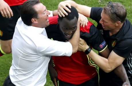 Belgium coach Marc Wilmots, left, and scorer Romelu Lukaku, center, celebrate the opening goal during the Euro 2016 Group E soccer match between Belgium and Ireland at the Nouveau Stade in Bordeaux, France, Saturday, June 18, 2016. (AP Photo/Andrew Medichini)