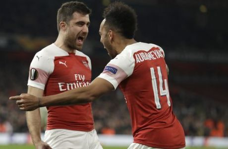 Arsenal's Sokratis Papastathopoulos, left, celebrates with Arsenal's Pierre-Emerick Aubameyang after scoring his side's third goal during the Europa League round of 32 second leg soccer match between Arsenal and Bate at the Emirates stadium in London, Thursday, Feb. 21, 2019. (AP Photo/Matt Dunham)