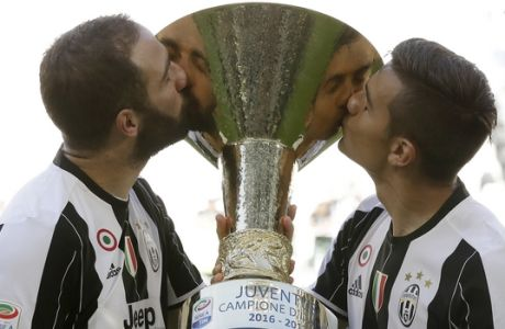 FILE - In this Sunday, May 21, 2017 file photo, Juventus' Gonzalo Higuain, left, and Juventus' Paulo Dybala kiss the trophy as Juventus players celebrate winning an unprecedented sixth consecutive Italian title, at the end of the Serie A soccer match between Juventus and Crotone at the Juventus stadium, in Turin, Italy.  Juventus will face Real Madrid in the Champions League final in Cardiff, Wales, on Saturday, June 3, 2017. (AP Photo/Antonio Calanni, File)