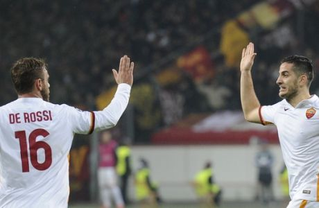Roma's Daniele De Rossi, left, celebrates with teammate Konstantinos Manolas after scoring his side's first goal during the Champions League group E soccer match between Bayer 04 Leverkusen and AS Roma in Leverkusen, Germany, Tuesday, Oct. 20, 2015. (AP Photo/Sebastian Konopka)
