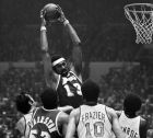 FILE - In this May 8, 1973 file photo, Los Angeles Lakers center Wilt Chamberlain towers over teammate Happy Hairston and New York Knicks players, from left, Dave DeBusschere, Walt Frazier and Earl Monroe, during an NBA playoff game at Madison Square Garden in New York. It's been 33 years since teams from these cities played for a title. The rivalry could be lost on many fans when the Kings and Rangers meet for the Stanley Cup. (AP Photo/File2)