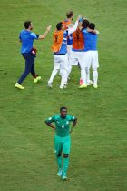 FORTALEZA, BRAZIL - JUNE 24: A dejected Kolo Toure of the Ivory Coast walks off as Greece celebrate their 2-1 win during the 2014 FIFA World Cup Brazil Group C match between Greece and the Ivory Coast at Castelao on June 24, 2014 in Fortaleza, Brazil.  (Photo by Robert Cianflone/Getty Images)