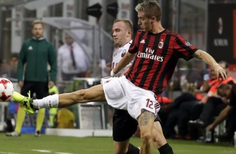 AC Milan's Andrea Conti, right, and Shkendija's Ivan Celikovic vie for the ball during the Europa League, play-off, first-leg soccer match between AC Milan and Shkendija, at the Milan San Siro Stadium, Italy, Thursday, Aug.17, 2017. (AP Photo/Antonio Calanni)