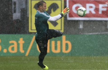 Germany goalkeeper Manuel Neuer catches the ball as hail falls during warmup before a friendly soccer match between Austria and Germany in Klagenfurt, Austria, Saturday, June 2, 2018. (AP Photo/Ronald Zak)