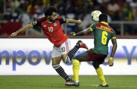 Egypt's Mohamed Salah, left, controls the ball in front of Cameroon's Ambroise Oyongo during the African Cup of Nations final soccer match between Egypt and Cameroon at the Stade de l'Amitie, in Libreville, Gabon, Sunday, Feb. 5, 2017. (AP Photo/Sunday Alamba)