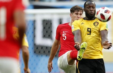 England's John Stones, background, and Belgium's Romelu Lukaku challenge for the ball during the third place match between England and Belgium at the 2018 soccer World Cup in the St. Petersburg Stadium in St. Petersburg, Russia, Saturday, July 14, 2018. (AP Photo/Natacha Pisarenko)