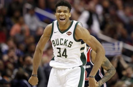 Milwaukee Bucks forward Giannis Antetokounmpo (34), from Greece, celebrates after making a shot over Washington Wizards forward Kelly Oubre Jr. (12) during the second half of an NBA basketball game Saturday, Jan. 6, 2018, in Washington. The Bucks won 110-103. (AP Photo/Alex Brandon)