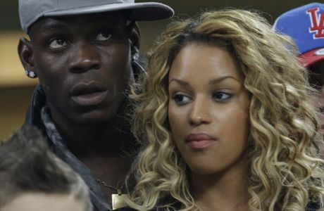 AC Milan striker Mario Balotelli and his girlfriend Fanny Neguesha wait for the start of the Champions League round of 16, first leg soccer match between AC Milan and Barcelona, at the San Siro stadium in Milan, Italy, Wednesday, Feb. 20, 2013. (AP Photo/Luca Bruno)