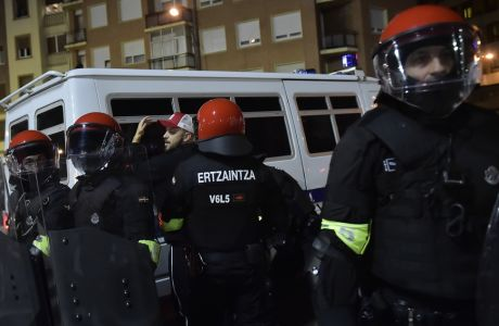 Basque riot police controls a follower of FC Spartak Moskva before the match during the Europa League - round of 32, 2nd leg, between Athletic Bilbao and FC Spartak Moskva, at San Mames stadium, in Bilbao, northern Spain, Thursday, Feb.22, 2018. (AP Photo/Alvaro Barrientos)