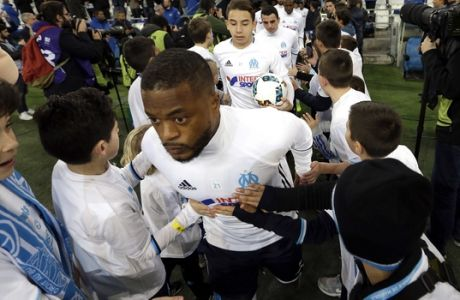 Children welcome Marseille's defender Patrice Evra and Marseille players, for a training session before the League One soccer match between Marseille and Paris Saint-Germain, at the Velodrome Stadium, in Marseille, southern France, Sunday, Feb. 26, 2017. (AP Photo/Claude Paris)