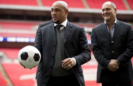Former Brazil national soccer team player Roberto Carlos holds a ball as he attends a group photo session pitchside as a guest of FIFA Presidential Candidate Gianni Infantino after unveiling his 90 day plan that he will implement if he is elected FIFA President, at Wembley Stadium in London, Monday, Feb. 1, 2016. (AP Photo/Matt Dunham)