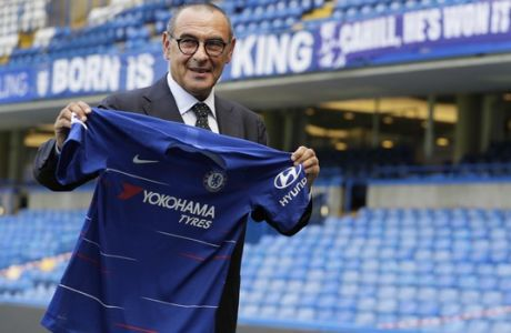 Maurizio Sarri, the new Chelsea team manager, holds up a shirt on the pitch as he is introduced to the media at Stamford Bridge stadium in London, Wednesday, July 18, 2018. (AP Photo/Kirsty Wigglesworth)