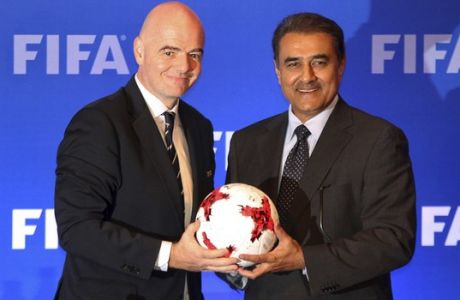 FIFA President Gianni Infantino, left, holds a soccer ball with All India Football Federation (AIFF) President Praful Patel during a press conference in Kolkata, India, Friday, Sept. 27, 2017. The finals of the FIFA U-17 World Cup India 2017 will be played between Spain and England on Saturday. (AP Photo)